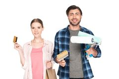 Smiling couple with credit card shopping bag and painting tools. Isolated on white background royalty free stock photo