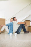 Smiling couple with cups and boxes in a new house Stock Photos