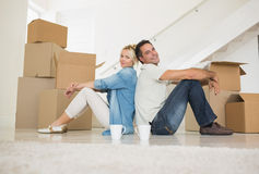 Smiling couple with cups and boxes in a new house Stock Images