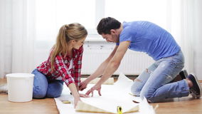 Smiling couple cutting wallpaper stock footage