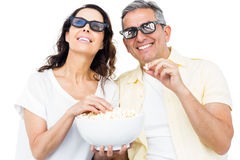 Smiling couple with 3D glasses eating popcorn Stock Images