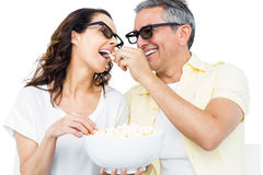 Smiling couple with 3D glasses eating popcorn Stock Photos