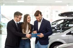 Cheerful buyers with car dealer in shop stock image