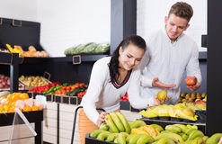 Smiling couple deciding on fruits in shop Stock Images