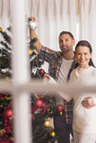Smiling couple decorating the christmas tree together. At home in the living room Stock Photos