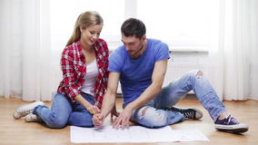 Smiling couple discussin blueprint at home Royalty Free Stock Image