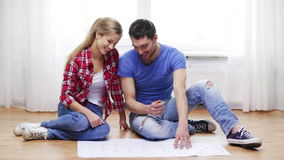 Smiling couple discussin blueprint at home Stock Image