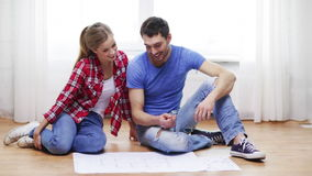 Smiling couple discussin blueprint at home Stock Images