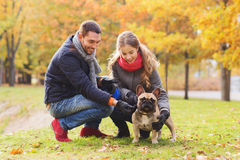 Smiling couple with dog in autumn park Royalty Free Stock Image