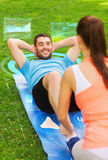 Smiling couple doing exercises on mat outdoors Royalty Free Stock Images