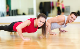 Smiling couple doing push-ups in the gym. Fitness, sport, training, gym and lifestyle concept - smiling couple doing push-ups in the gym royalty free stock image