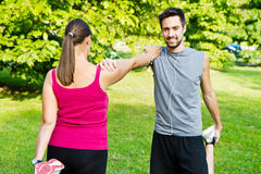 Smiling couple doing streching in the park. A couple doing streching in the park Royalty Free Stock Photos