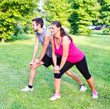 Smiling couple doing streching in the park. A smiling couple doing streching in the park Royalty Free Stock Photos