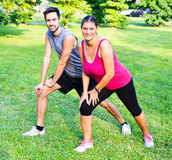 Smiling couple doing streching in the park. A smiling couple doing streching in the park Royalty Free Stock Image