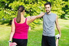 A smiling couple doing streching in the park. Smiling couple doing streching in the park Stock Photography