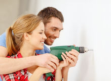 Smiling couple drilling hole in wall at home Royalty Free Stock Photos