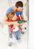 Smiling couple drilling hole in wall at home Royalty Free Stock Photography