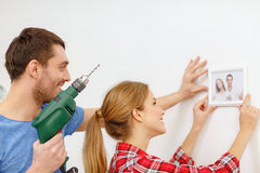 Smiling couple drilling hole in wall at home. Repair, interior design, building, renovation and home concept - smiling couple drilling hole in wall and putting stock photos
