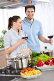 Smiling couple drink red wine cooking in kitchen Stock Photos