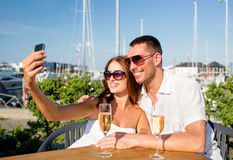Smiling couple drinking champagne at cafe Royalty Free Stock Photos