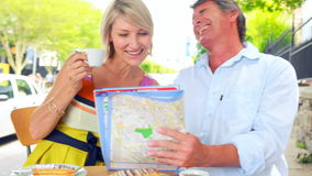 Smiling couple drinking coffee and checking the map stock footage