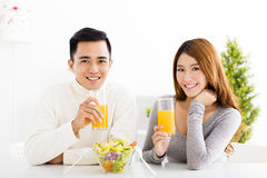 Smiling couple drinking juice and healthy food Stock Photos