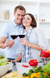 Smiling couple drinking wine while cooking. In the kitchen Stock Image