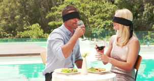 Smiling couple drinking wine with hidden eyes. Poolside stock footage