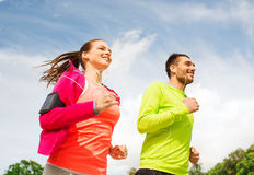 Smiling couple with earphones running outdoors. Fitness, sport, friendship and lifestyle concept - smiling couple with earphones running outdoors Stock Images