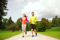 Smiling couple with earphones running outdoors Stock Image