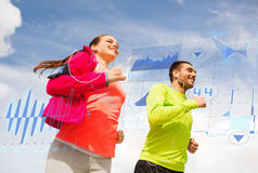 Smiling couple with earphones running outdoors Stock Photos