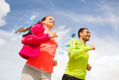 Smiling couple with earphones running outdoors Royalty Free Stock Photos