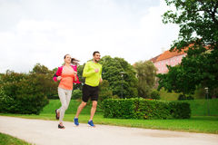 Smiling couple with earphones running outdoors Royalty Free Stock Photography
