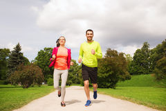 Smiling couple with earphones running outdoors Stock Photography