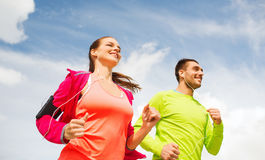 Smiling couple with earphones running outdoors Royalty Free Stock Photo