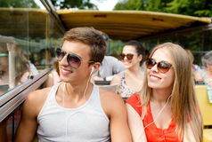 Smiling couple with earphones traveling by bus Stock Photo