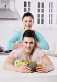 Smiling couple eat salad in the kitchen Royalty Free Stock Photos