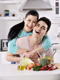 Smiling couple eat salad in the kitchen Royalty Free Stock Image