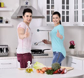 Smiling couple eat salad in the kitchen Royalty Free Stock Photography