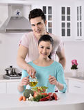Smiling couple eat salad in the kitchen Stock Photos