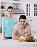 Smiling couple eat salad in the kitchen Stock Image