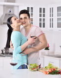 Smiling couple eat salad in the kitchen Royalty Free Stock Images