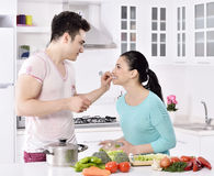 Smiling couple eat salad in the kitchen Stock Photo