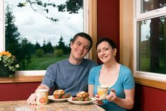 A Smiling Couple Eating Breakfast At Home Royalty Free Stock Image