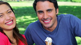 Smiling couple eating cones stock footage