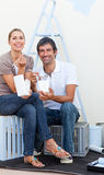 Smiling couple eating while decorating a room. After move in Stock Photography