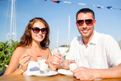 Smiling couple eating dessert at cafe Stock Images