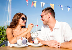 Smiling couple eating dessert at cafe Stock Image