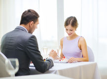 Smiling couple eating dessert at restaurant Stock Image