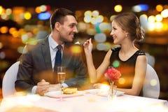 Smiling couple eating dessert at restaurant. Restaurant, couple and holiday concept - smiling couple eating dessert at restaurant royalty free stock images